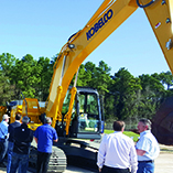 A group of dealer sales professionals gather around KOBELCO's new Generation 10 SK210 excavator to learn the benefits of its innovative features